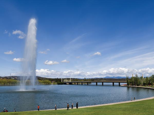 Fountain, Sky, Water, Water resources, Daytime, Cloud, Water feature, Architecture, Reflecting pool, River, Lake, Reservoir, Tourist attraction, Tourism, Lake Burley Griffin, Telstra Tower, Parliament House